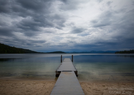 Idaho, North, Coolin. A dock extends over calm water under stormy skies at the Indian Creek Unit of Priest Lake State Park.