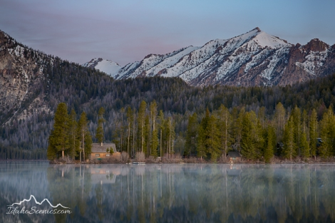 Idaho, South central, Stanley, A cabin on the shore of Pettit Lake at dawn in spring with calm water and reflections.