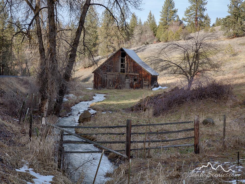 Idaho, North Central, Idaho County, Kooskia. An old barn and creek in winter.
